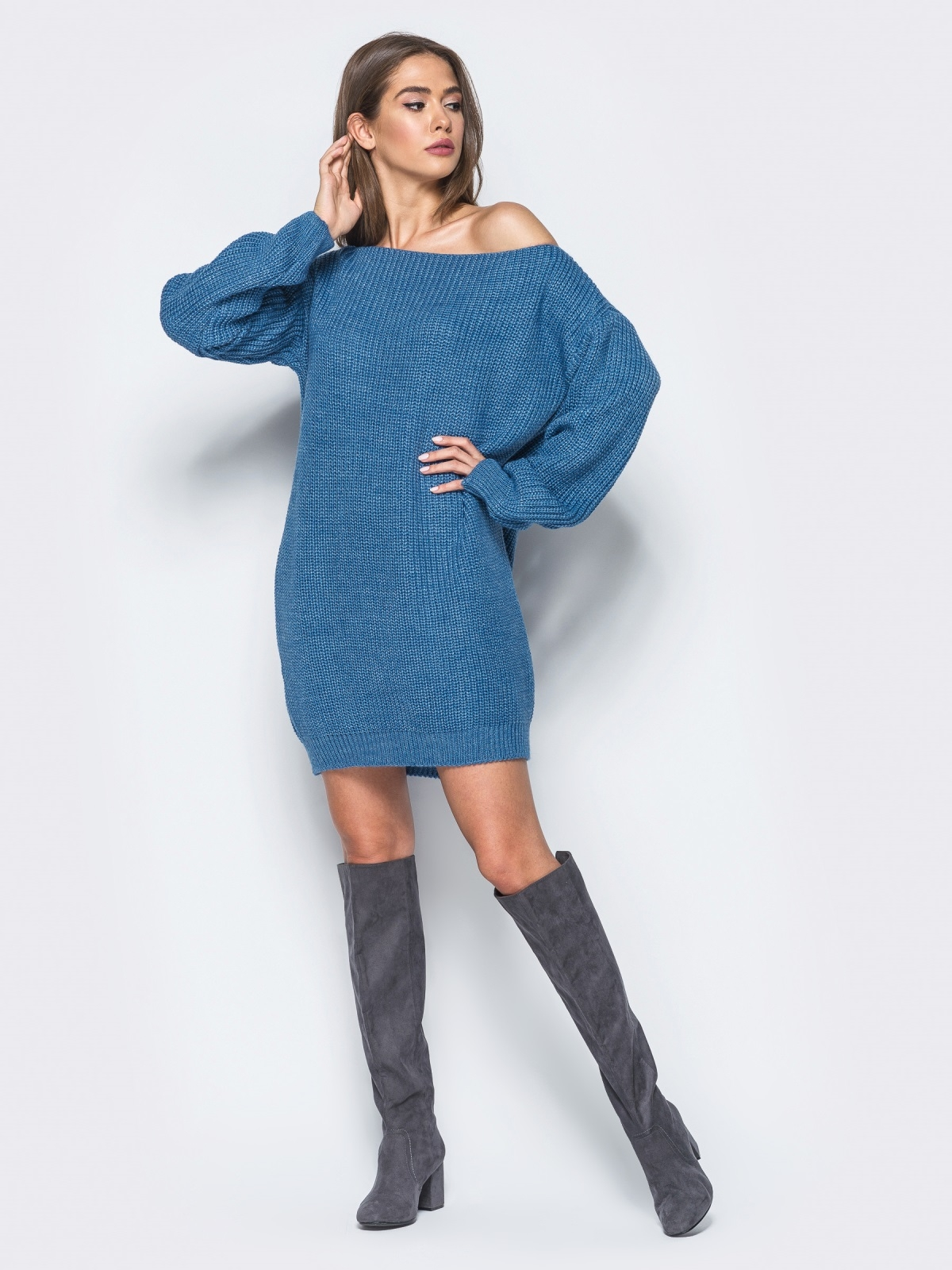 Шатенка позирует в синем вязаном платье с открытыми плечами