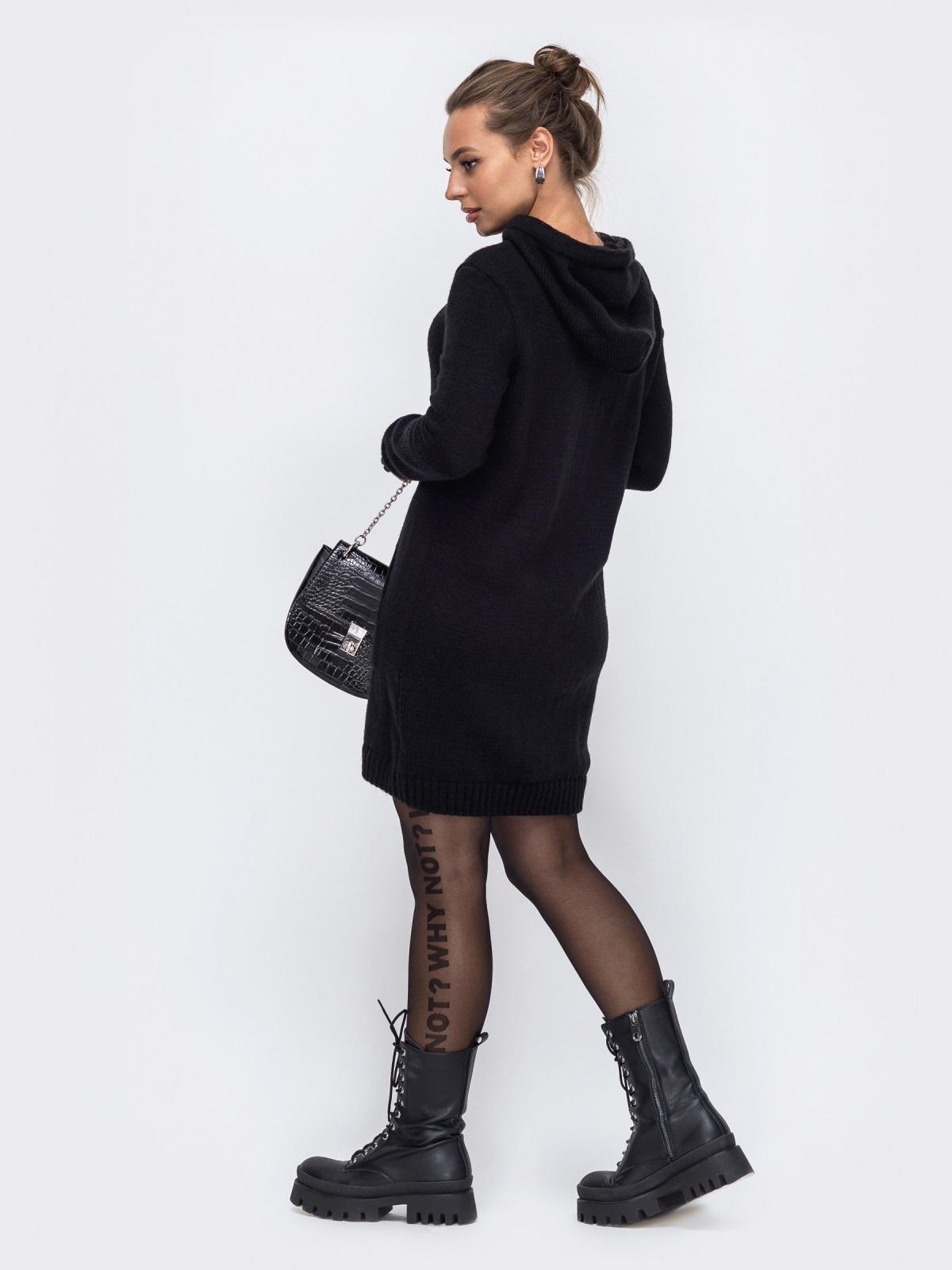 Девушка позирует в черной вязаной тунике с капюшоном под ботинки